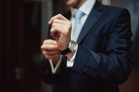 Photo pour The man fastens the watch on his hand - image libre de droit