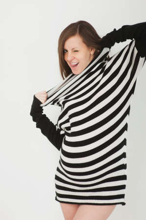 Beautiful fashion pregnant young happy brunette woman in striped black white dress with big belly, tummy. Pregnancy, parenthood, family, motherhood, parents, children, people and expectation concept