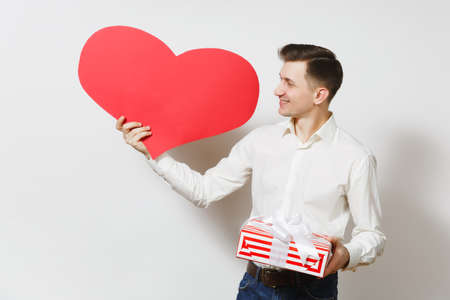 Young handsome smiling man in shirt holding red present box with gift isolated on white background. Copy space for advertisement. St. Valentines Day, International Womens Day birthday holiday concept