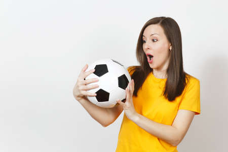Beautiful European young cheerful happy woman, football fan or player in yellow uniform holding soccer ball isolated on white background. Sport, play football, health, healthy lifestyle concept