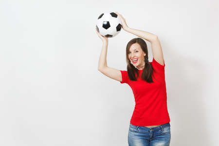 Active European young woman, two fun pony tails, football fan or player in red uniform catching classic soccer ball isolated on white background. Sport play football health, healthy lifestyle concept