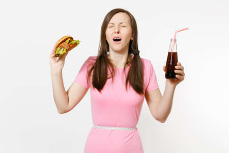 Sad young woman with tails, measuring tape at waist holding burger, cola in glass bottle isolated on white background. Proper nutrition or American classic fast food. Advertising area with copy spaceの写真素材