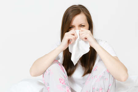 Young sickness tired brunette woman in pajamas sitting on bed isolated on white background. Female feeling bad, blowing her nose into white napkin. Cold in the head. Copy space for advertisement