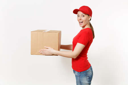 Photo pour Delivery woman in red uniform isolated on white background. Female in cap, t-shirt, jeans working as courier or dealer holding cardboard box. Receiving package. Copy space advertisement. Side view - image libre de droit