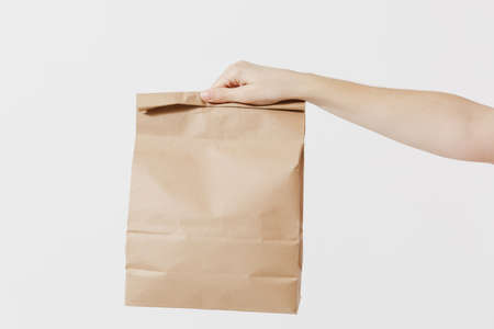 Close up female holds in hand brown clear empty blank craft paper bag for takeaway isolated on white background. Packaging template mockup. Delivery service concept. Copy space. Advertising area