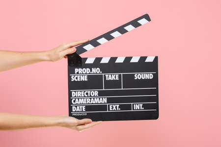 Foto de Close up female holding in hand classic director clear empty black film making clapperboard isolated on trending pastel pink background. Cinematography production concept. Copy space for advertising - Imagen libre de derechos