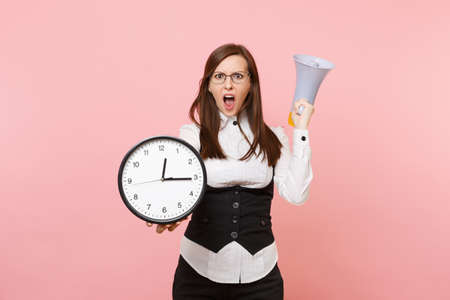 Young shocked business woman in suit glasses screaming holding megaphone and alarm clock isolated on pastel pink background. Lady boss. Achievement career wealth concept. Copy space for advertisement