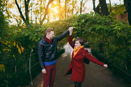 Young happy couple in love, attractive happy woman and man in casual warm clothes dancing and whirling walking near green arch in autumn city park outdoors. Love relationship family lifestyle concept