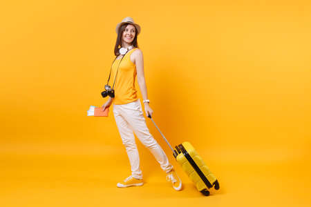 Photo for Traveler tourist woman in summer casual clothes, hat with headphones on neck isolated on yellow orange background. Passenger traveling abroad to travel on weekends getaway. Air flight journey concept - Royalty Free Image