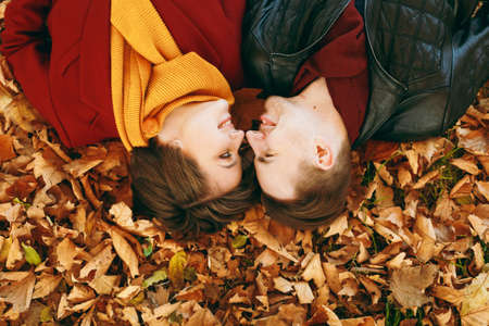 Top view Portrait of young romantic couple in love woman and man looking at each other touching noses lying on fallen leaves in autumn city park outdoors. Love relationship family lifestyle concept