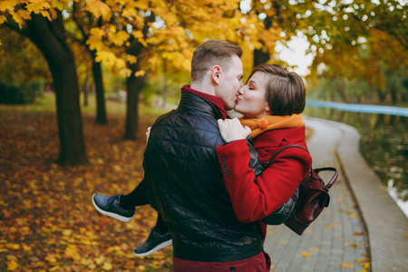Back view Young couple in love handsome man holding woman in arms embracing kissing with closed eyes on walk near water in autumn city park outdoors. Love relationship family people lifestyle concept