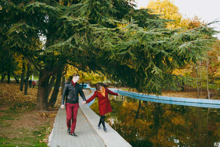 Young joyful couple in love woman and man in warm clothes holding hands having fun walking on road near water? coniferous trees in autumn city park outdoors. Love relationship family people lifestyle