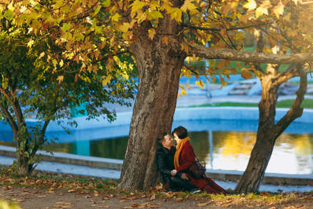 Young laughing happy couple in love woman and man looking at each other sitting on fallen leaves near tree and water in autumn city park outdoors. Love relationship family people lifestyle concept