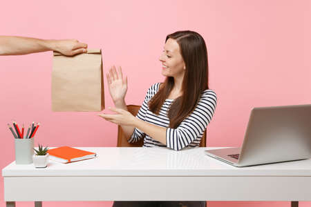 Woman taking brown clear empty blank craft paper bag, work at office with pc laptop isolated on pink background. Food products delivery courier service from shop or restaurant to office.
