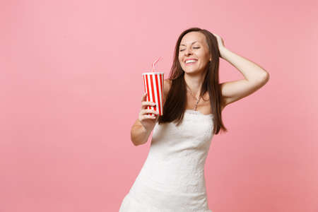 Foto de Portrait of smiling bride woman with closed eyes in white wedding dress keeping hand on head holding plastic cup with cola or soda isolated on pink pastel background. Wedding celebration. Copy space - Imagen libre de derechos