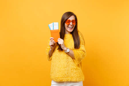Cheerful laughing young woman with closed eyes in orange heart glasses holding passport boarding pass tickets isolated on bright yellow background. People sincere emotions lifestyle. Advertising area