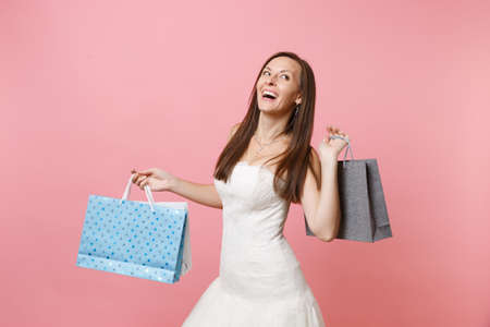 Foto de Portrait of cheerful bride woman in wedding dress looking up holding multi colored packages bags with purchases after shopping isolated on pink background. Organization of wedding concept. Copy space - Imagen libre de derechos