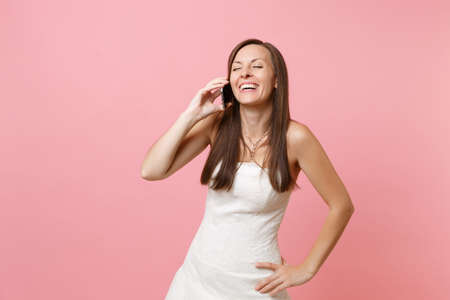 Foto de Laughing bride woman in white wedding dress talking on mobile phone, conducting pleasant conversation isolated on pastel pink background. Wedding to do list. Organization of celebration. Copy space - Imagen libre de derechos