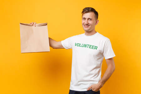 Photo for Portrait of man in white t-shirt written inscription green title volunteer hold blank craft paper bag for takeaway isolated on yellow background. Voluntary free assistance help charity grace concept - Royalty Free Image
