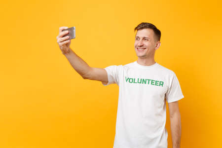 Photo for Portrait of man in white t-shirt written inscription green title volunteer taking selfie shot on mobile phone isolated on yellow background. Voluntary free assistance help charity grace work concept - Royalty Free Image
