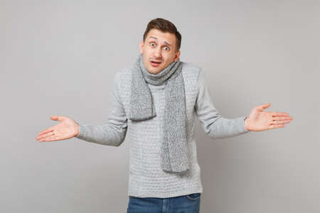 Perplexed young man in gray sweater, scarf spreading hands isolated on grey wall background studio portrait. Healthy fashion lifestyle people sincere emotions, cold season concept. Mock up copy space