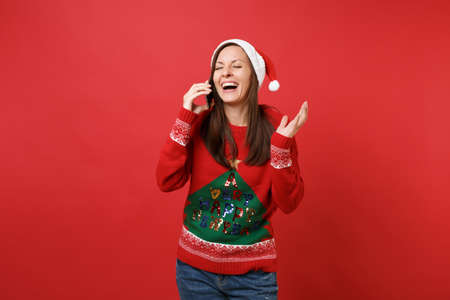 Photo pour Laughing young Santa girl spreading hand talking on mobile phone conducting pleasant conversation isolated on red background. Happy New Year 2019 celebration holiday party concept. Mock up copy space - image libre de droit