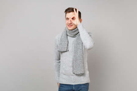 Attractive young man in gray sweater, scarf showing OK gesture near eye isolated on grey wall background. Healthy fashion lifestyle, people sincere emotions, cold season concept. Mock up copy space