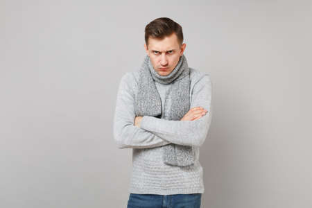 Strict young man in gray sweater, scarf holding hands crossed isolated on grey wall background in studio. Healthy fashion lifestyle, people sincere emotions, cold season concept. Mock up copy space