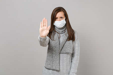 Photo pour Young woman in sweater, scarf with sterile face mask showing stop gesture with palm isolated on grey background. Healthy lifestyle, ill sick disease treatment, cold season concept. Mock up copy space - image libre de droit