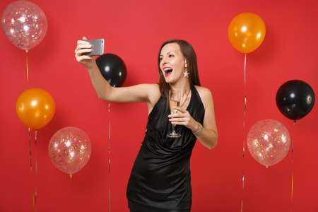 Foto de Excited young woman in black dress holding glass of champagne, doing taking selfie shot on mobile phone on bright red background air balloons. Happy New Year, birthday mockup holiday party concept - Imagen libre de derechos