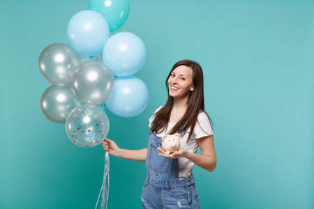 Foto de Portrait of smiling young woman in denim clothes holding piggy money bank celebrating with colorful air balloons isolated on blue turquoise background. Birthday holiday party, people emotions concept - Imagen libre de derechos