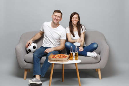 Photo pour Fun couple woman man football fans in white t-shirt cheer up support favorite team with soccer ball isolated on grey wall background in studio. People emotions, sport family leisure lifestyle concept - image libre de droit