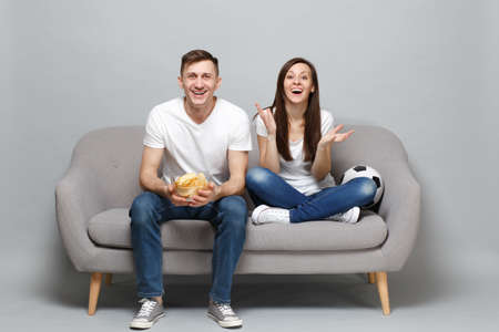 Photo pour Joyful couple woman man football fans cheer up support favorite team with soccer ball, holding glass bowl of chips isolated on grey background. People emotions, sport family leisure lifestyle concept - image libre de droit