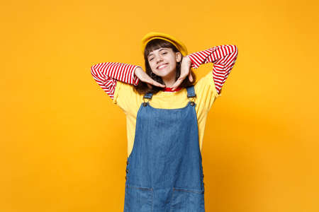 Photo for Portrait of charming girl teenager in french beret, denim sundress keeping hands near face isolated on yellow wall background in studio. People sincere emotions, lifestyle concept. Mock up copy space - Royalty Free Image