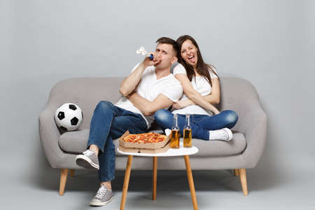 Photo pour Crazy couple woman man football fans in white t-shirt cheer up support favorite team blowing in pipe, sitting isolated on grey wall background. People emotions, sport family leisure lifestyle concept - image libre de droit