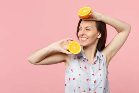 Foto de Smiling young woman in summer clothes looking aside holding two halfs of fresh ripe orange fruit isolated on pink pastel background. People vivid lifestyle relax vacation concept. Mock up copy space - Imagen libre de derechos