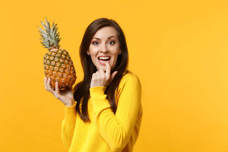 Foto de Cheerful young woman in casual clothes gnawing nails, hold in hands fresh ripe pineapple fruit isolated onyellow orange background. Peoplevivid lifestyle, relax vacation concept. Mock up copy space - Imagen libre de derechos