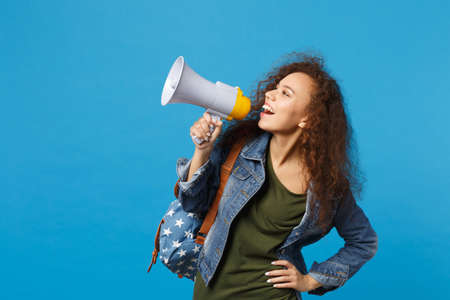 Photo pour Young african american girl teen student in denim clothes, backpack hold megaphone isolated on blue background studio portrait. Education in high school university college concept. Mock up copy space - image libre de droit