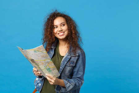 Young african american girl teen student in denim clothes, backpack hold map isolated on blue wall background studio portrait. Education in high school university college concept. Mock up copy space