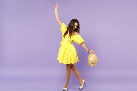 Smiling young woman in yellow dress holding summer hat, standing looking down spreading hands isolated on pastel violet wall background. People sincere emotions, lifestyle concept. Mock up copy space