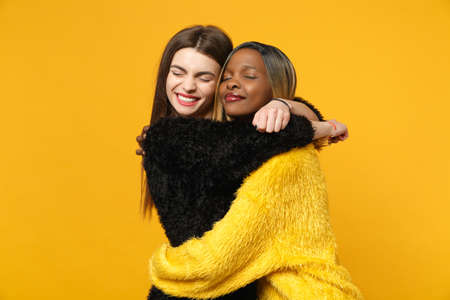 Foto de Two young women friends european and african american in black yellow clothes standing posing isolated on bright orange wall background, studio portrait. People lifestyle concept. Mock up copy space - Imagen libre de derechos