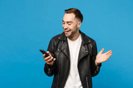 Handsome overjoyed excited young unshaven man in black leather jacket white t-shirt using mobile phone isolated on blue wall background studio portrait. People lifestyle concept. Mock up copy space
