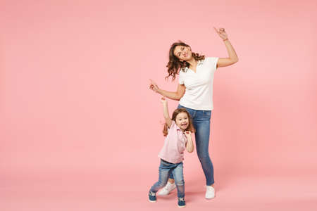 Foto de Woman in light clothes have fun with cute child baby girl. Mother, little kid daughter isolated on pastel pink wall background, studio portrait. Mother's Day love family, parenthood childhood concept - Imagen libre de derechos