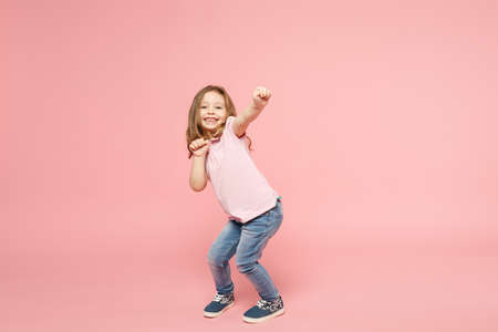 Little cute child kid baby girl 3-4 years old wearing light clothes dancing isolated on pastel pink wall background, children studio portrait. Mother's Day, love family, parenthood childhood concept