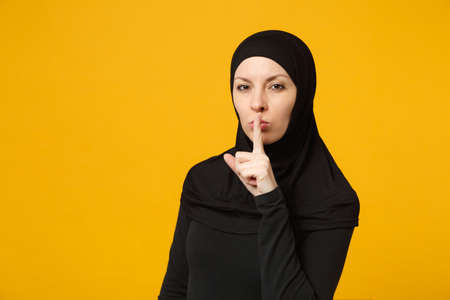 Photo pour Arabian muslim woman in hijab black clothes saying hush be quiet with finger on lips shhh gesture isolated on yellow background studio portrait. People religious lifestyle concept. Mock up copy space - image libre de droit