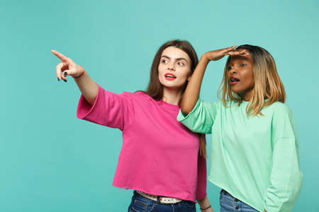 Foto de Two women friends european and african american in pink green clothes holding hand at forehead looking far away isolated on blue turquoise background. People lifestyle concept. Mock up copy space - Imagen libre de derechos