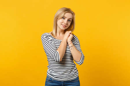 Photo pour Portrait of pretty young woman in striped clothes looking camera, holding hair isolated on yellow orange wall background in studio. People sincere emotions, lifestyle concept. Mock up copy space. - image libre de droit