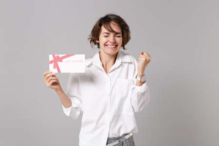Photo pour Joyful young business woman in white shirt posing isolated on grey background in studio. Achievement career wealth business concept. Mock up copy space. Hold gift certificate doing winner gesture. - image libre de droit