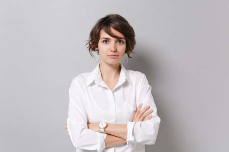 Foto de Beautiful young business woman in white shirt posing isolated on grey background studio portrait. Achievement career wealth business concept. Mock up copy space. Holding hands crossed, looking camera. - Imagen libre de derechos