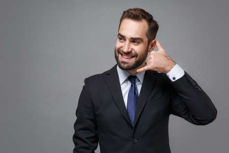 Photo pour Smiling young business man in classic suit shirt tie posing isolated on grey background. Achievement career wealth business concept. Mock up copy space. Doing phone gesture like says call me back. - image libre de droit